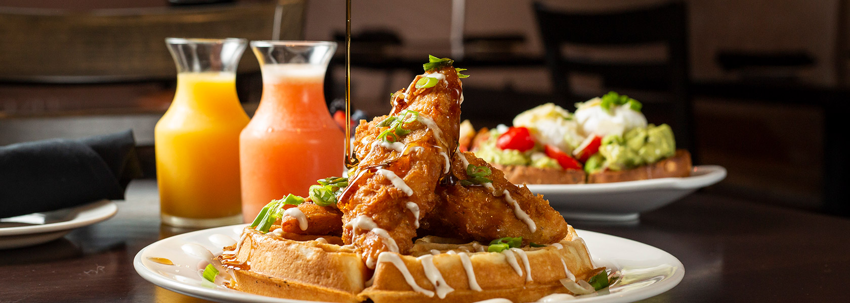 Syrup being drizzled over fried chicken on waffles with breakfast juices in background