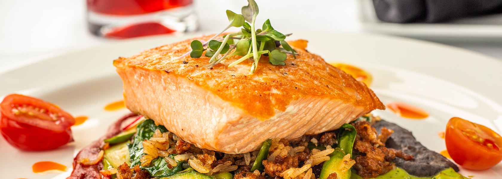 Pan-seared salmon plated on wild rice with cocktail