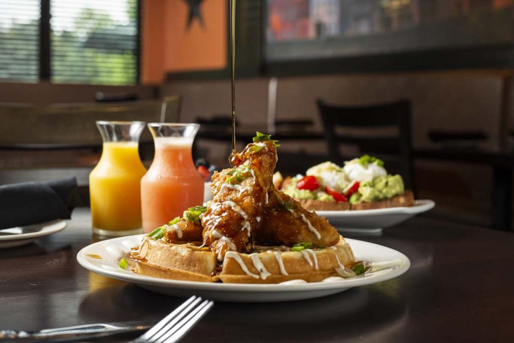 Syrup being drizzled over chicken and waffles with breakfast juices in background
