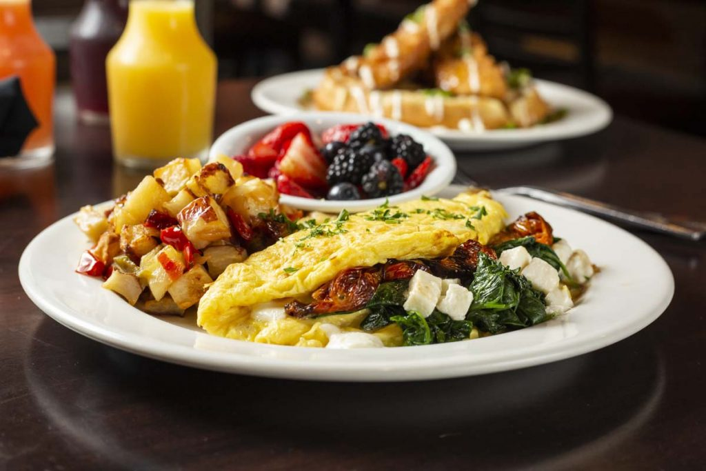 Omelet stuffed with mushrooms, cheese and spinach served with hashed browns, fruit cup in background