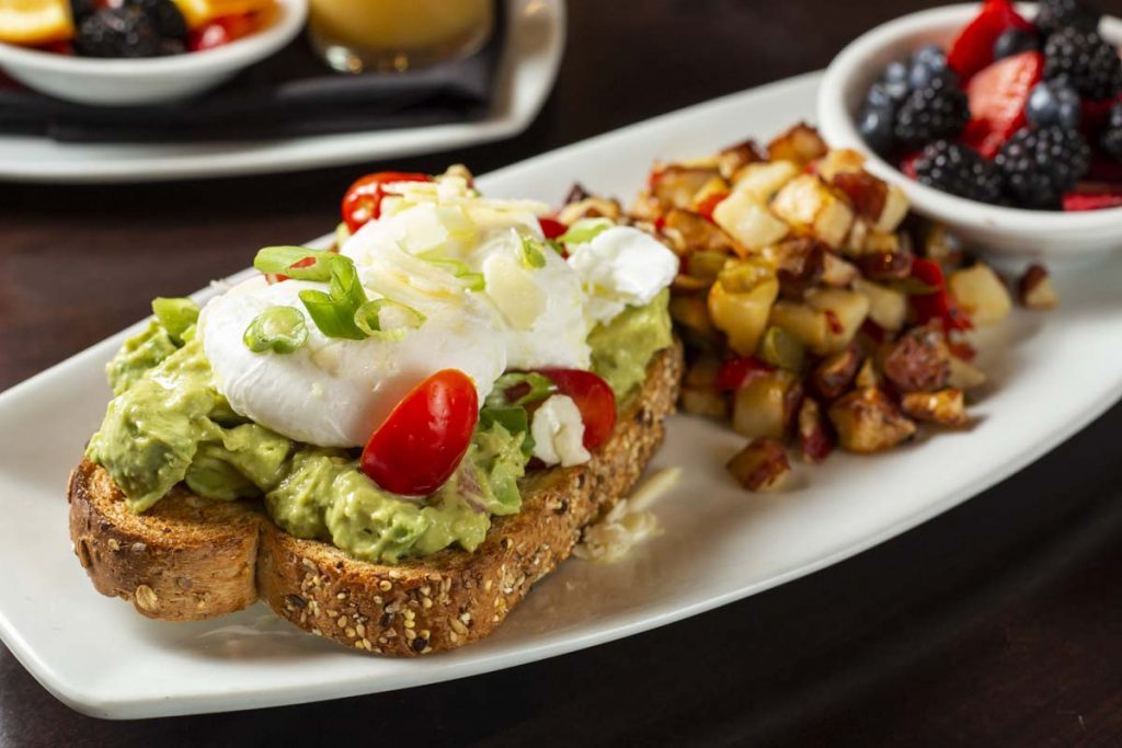 Avocado toast with hashed brown potatoes, fruit cup and breakfast juices in background