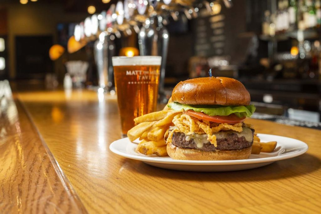 Matt the Miller's burger garnished with fried onions and served with French fries and glass of draft beer