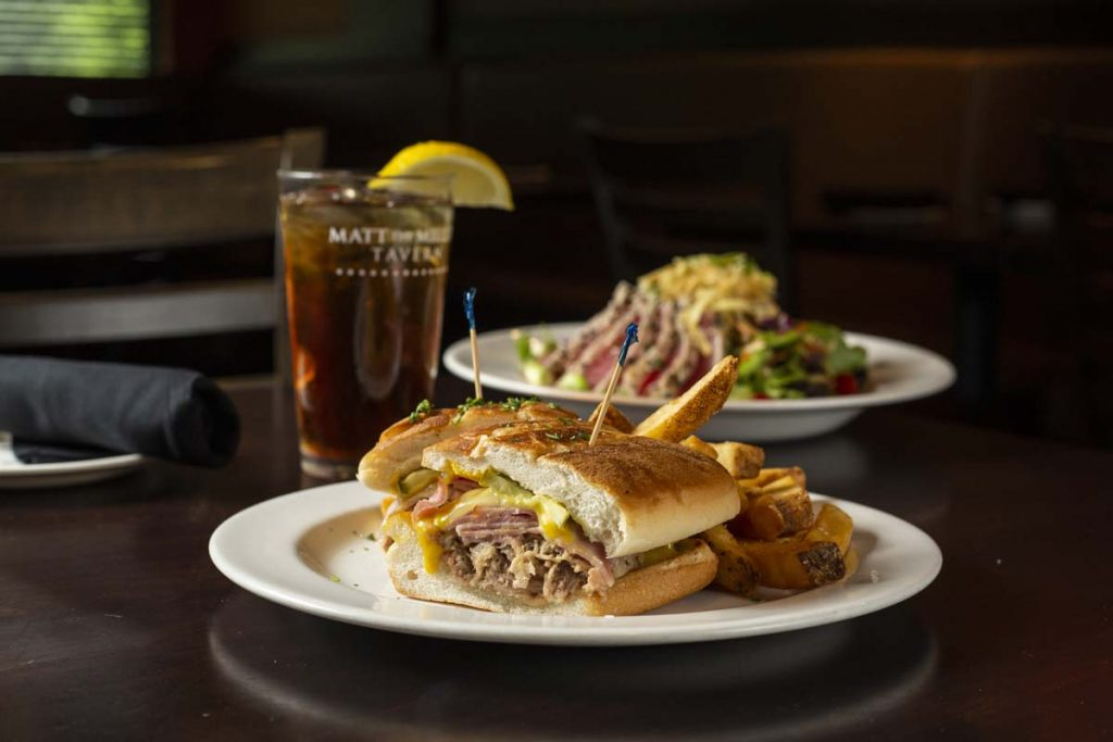 Grilled Cuban sandwich with French fries and glass of iced tea garnished with lemon wedge