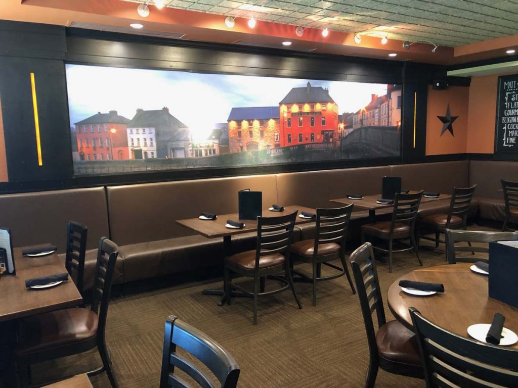Indoor dining room with wall mural of Irish pubs at Matt the Miller's Tavern in Dublin, Ohio