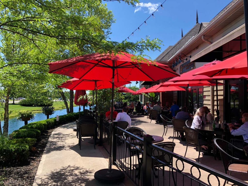 Outdoor patio seating with red umbrellas at Matt the Miller's Tavern in Dublin, Ohio