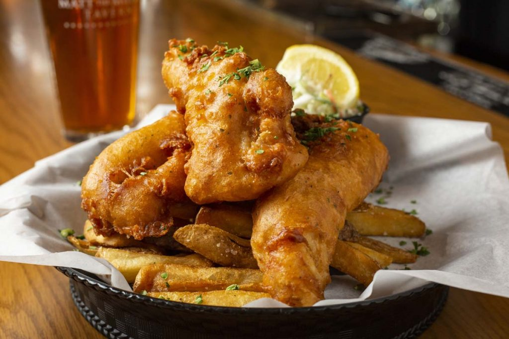 Three pieces of fried fish arranged on fries with lemon wedge