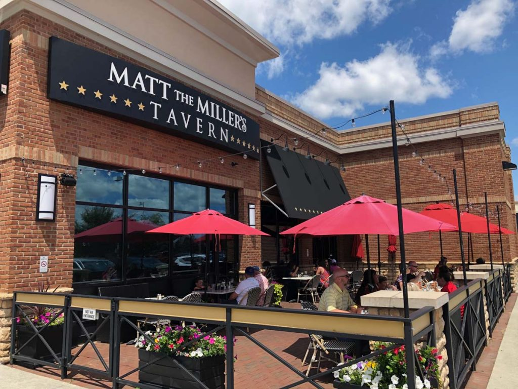 Exterior view of Matt the Miller's patio with red umbrellas and seating at Gemini Place in Ohio