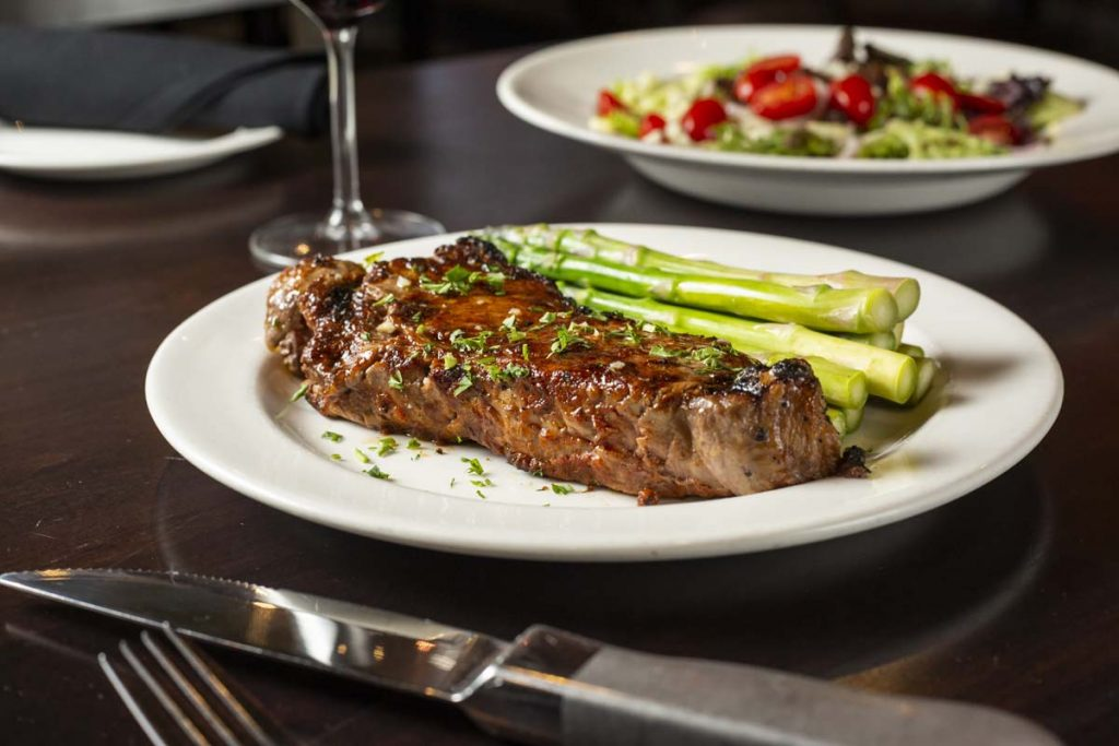 New York Strip Steak plated with asparagus and white wine with salad