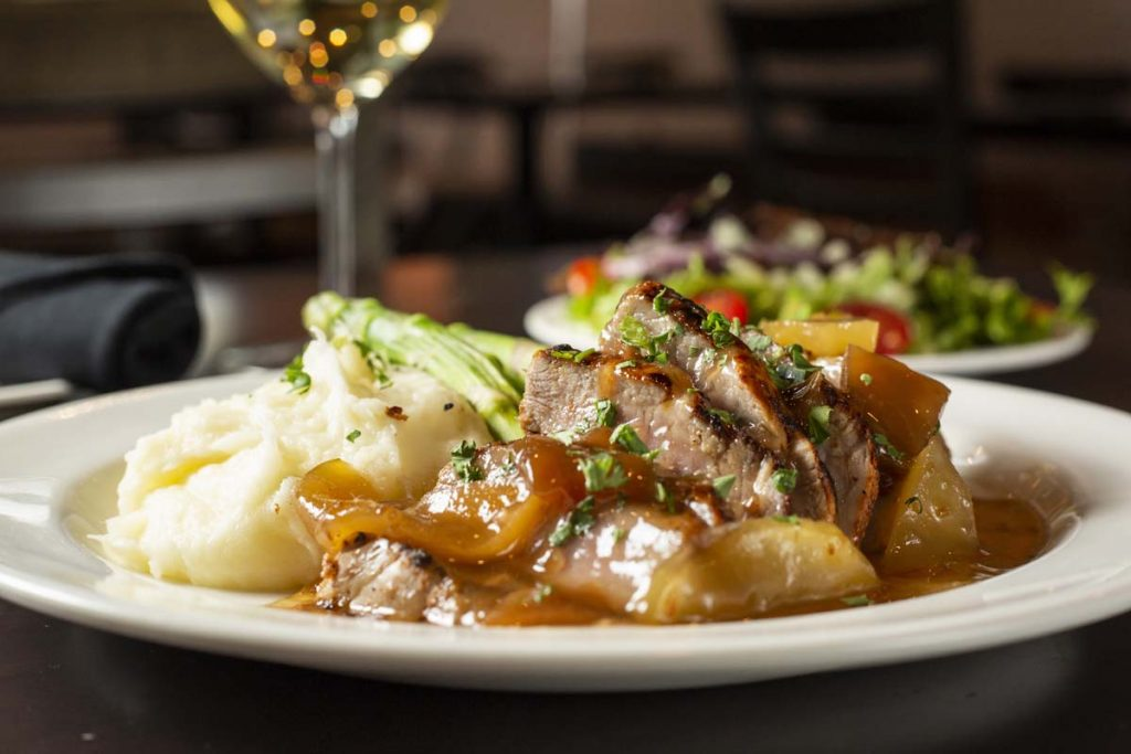 Plated roast pork entree with apple gravy and mashed potatoes with glass of white wine