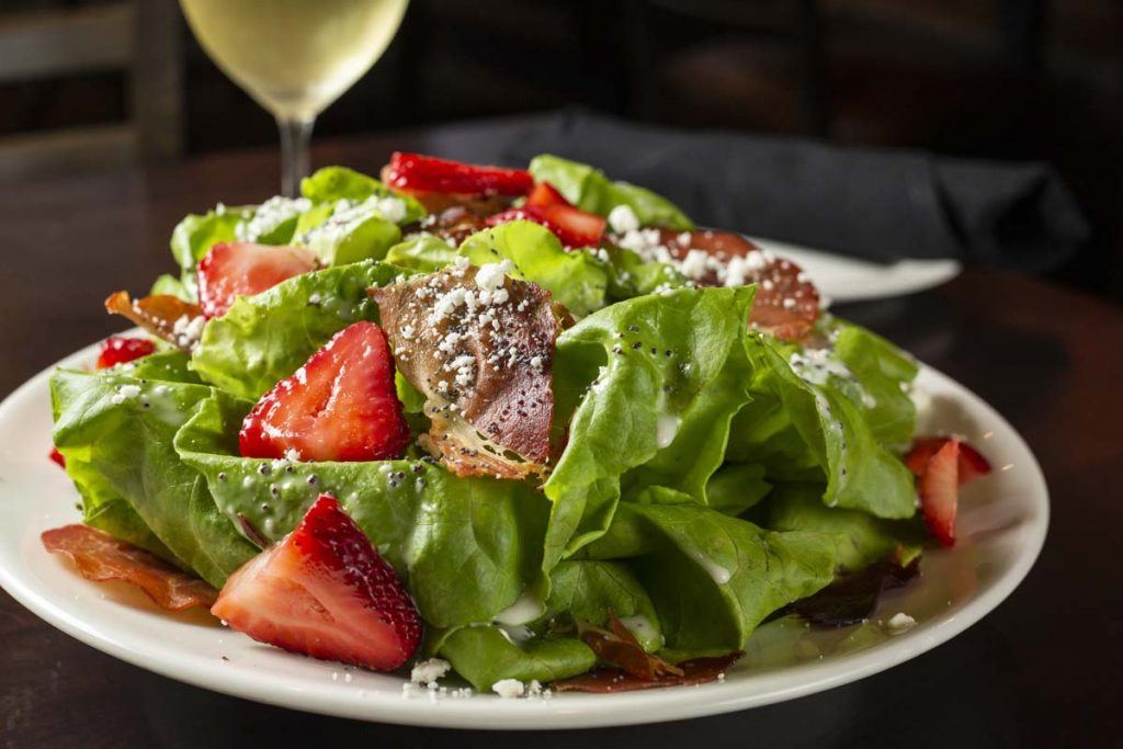 Bibb lettuce salad with strawberries and glass of white wine