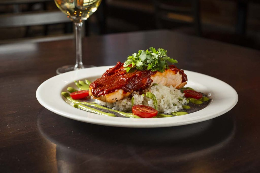 Plated Baja Salmon dish with sauce and white wine