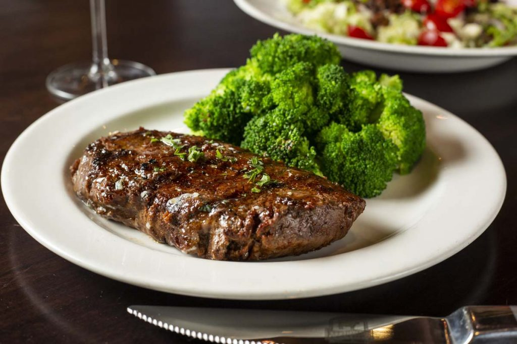 Plated sirloin steak with broccoli and glass of wine