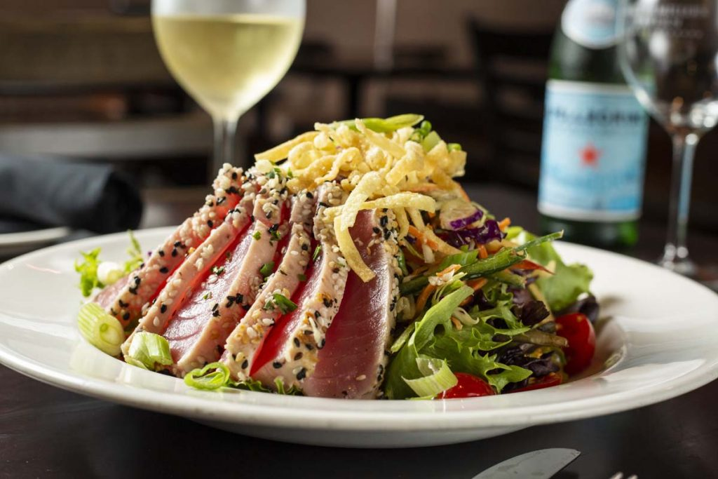 Seared Ahi Tuna slices plated on bed of lettuce with glass of white wine