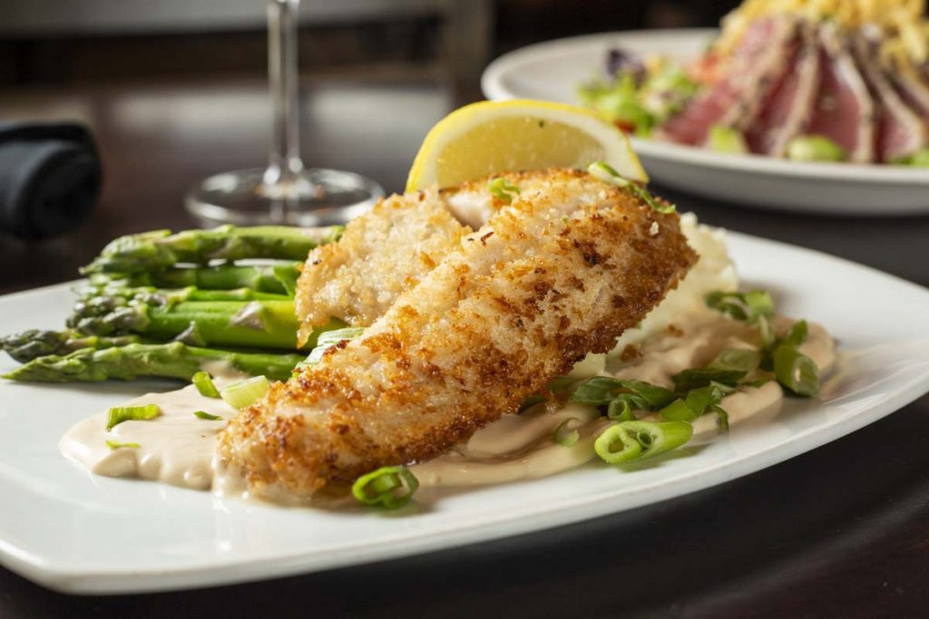Plated walleye fish on potatoes with asparagus and glass of white wine