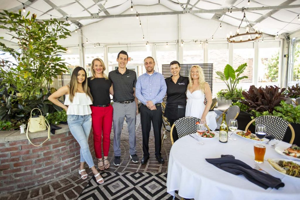 Group of six people, guests and staff, standing together in three-season covered patio.