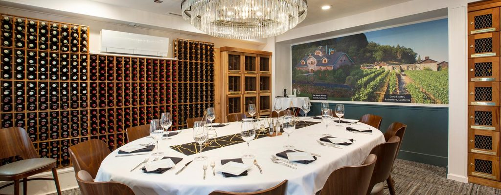Private dining room lined with wine racks and wine lockers, table set for service for 12.