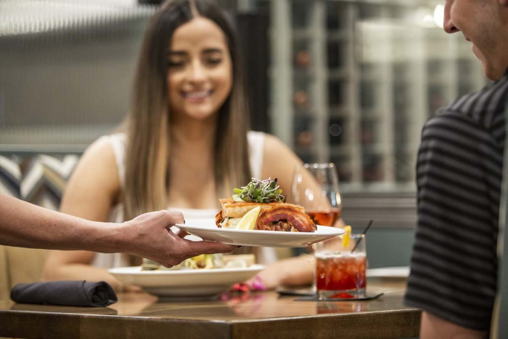 Woman smiles as entree is presented to her