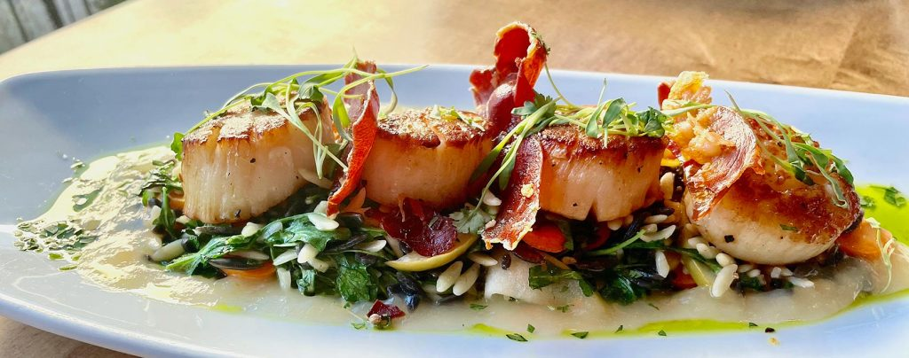 Four pan-seared scallops with bacon garnish and butter sauce.