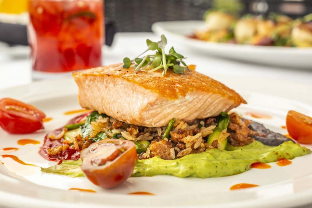 Tucci's pan-seared salmon on bed of wild rice with cocktail in background