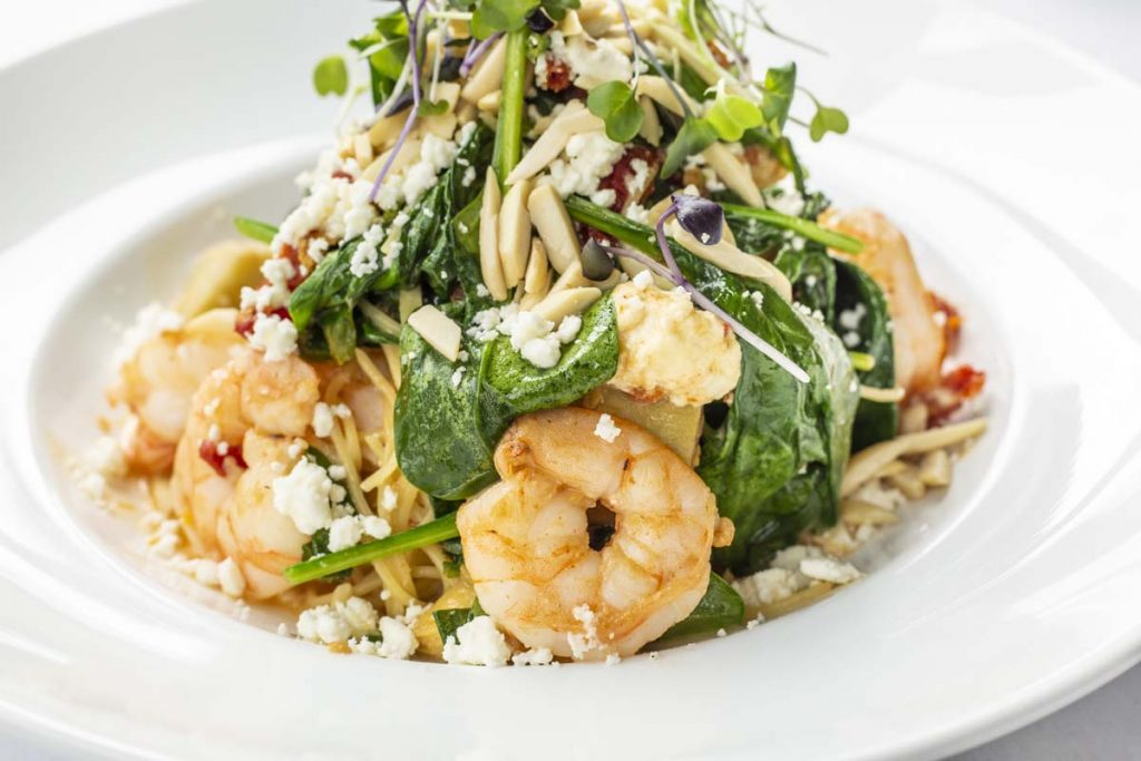 Tucci's Shrimp with orzo pasta topped with salad greens