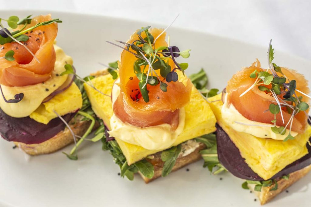 Tucci's Smoked Salmon Toast brunch entree with thin slices of smoked salmon on scrambled egg and watercress on toast